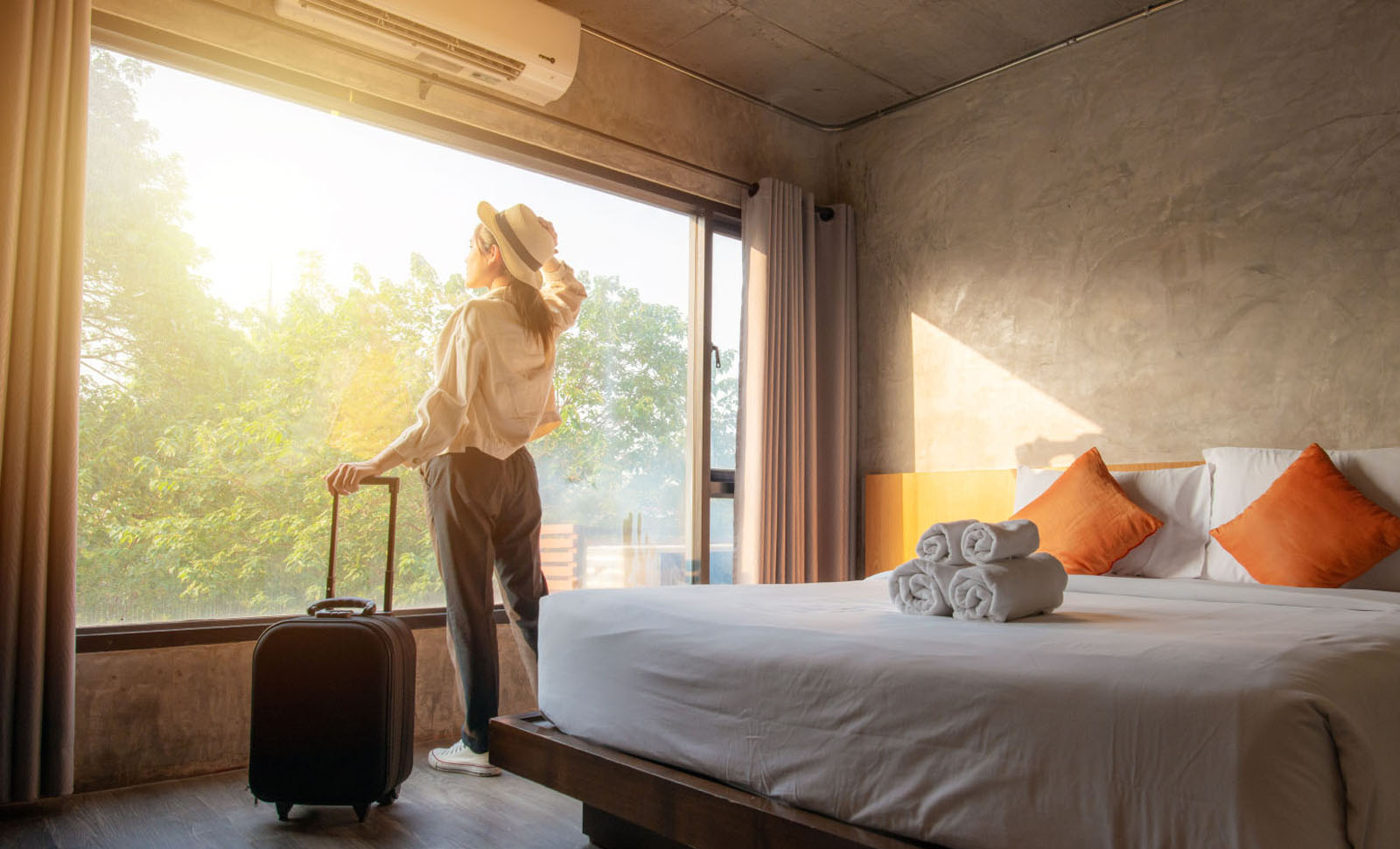 Woman looking out the window of her hotel room holding her luggage in one hand.