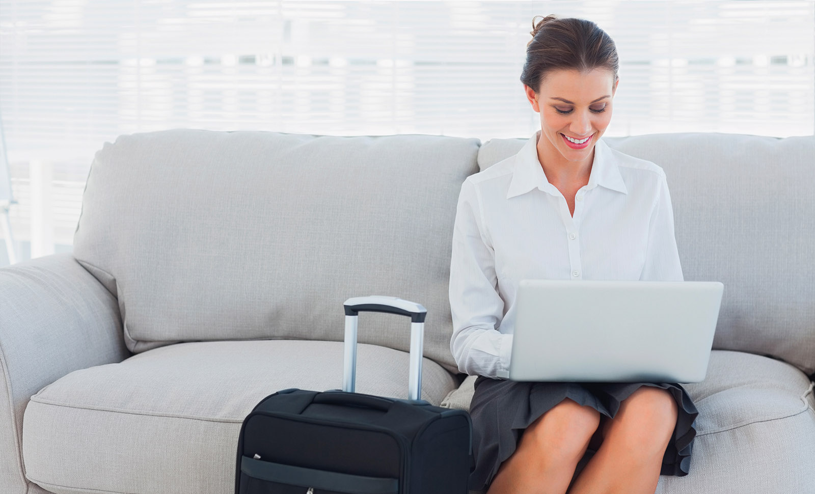 woman sitting on couch in hotel room working on her laptop with her suitcase next to her