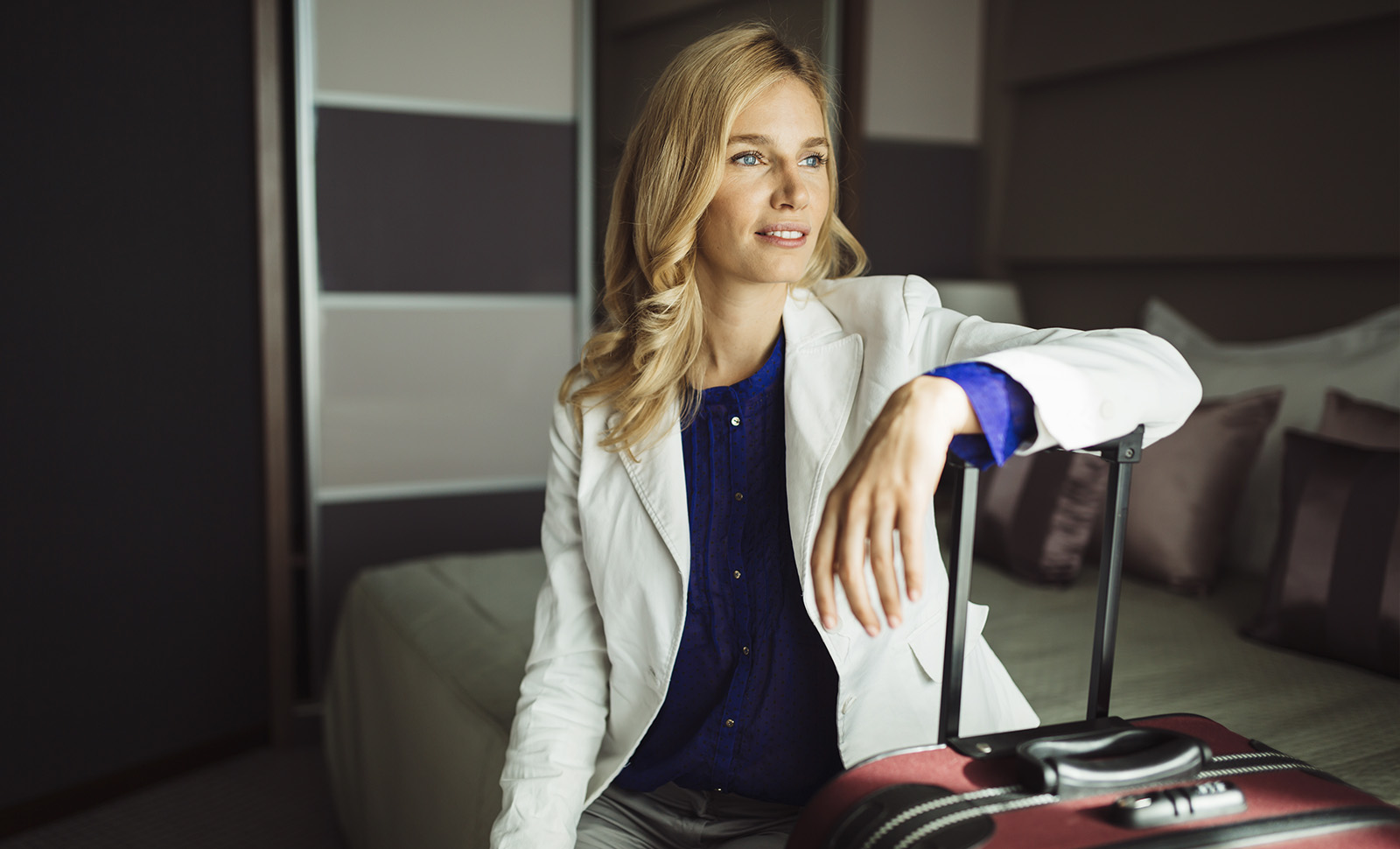 woman sitting on a hotel bed with her arm resting on her suitcase