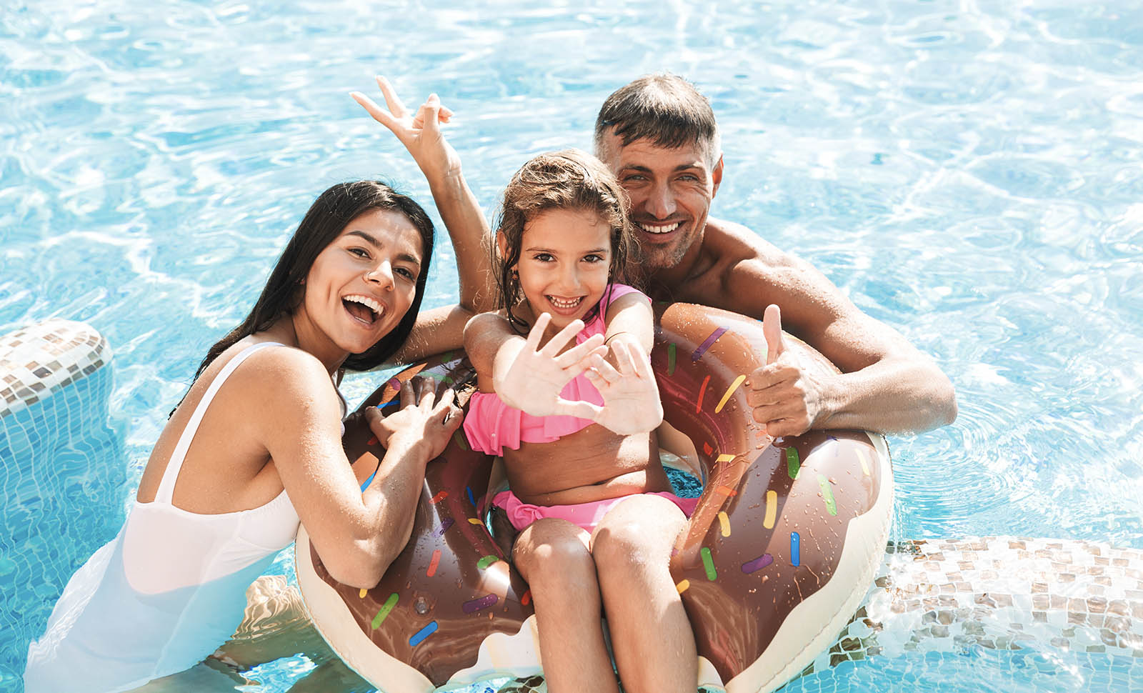 family laughing and taking a photo together in a pool