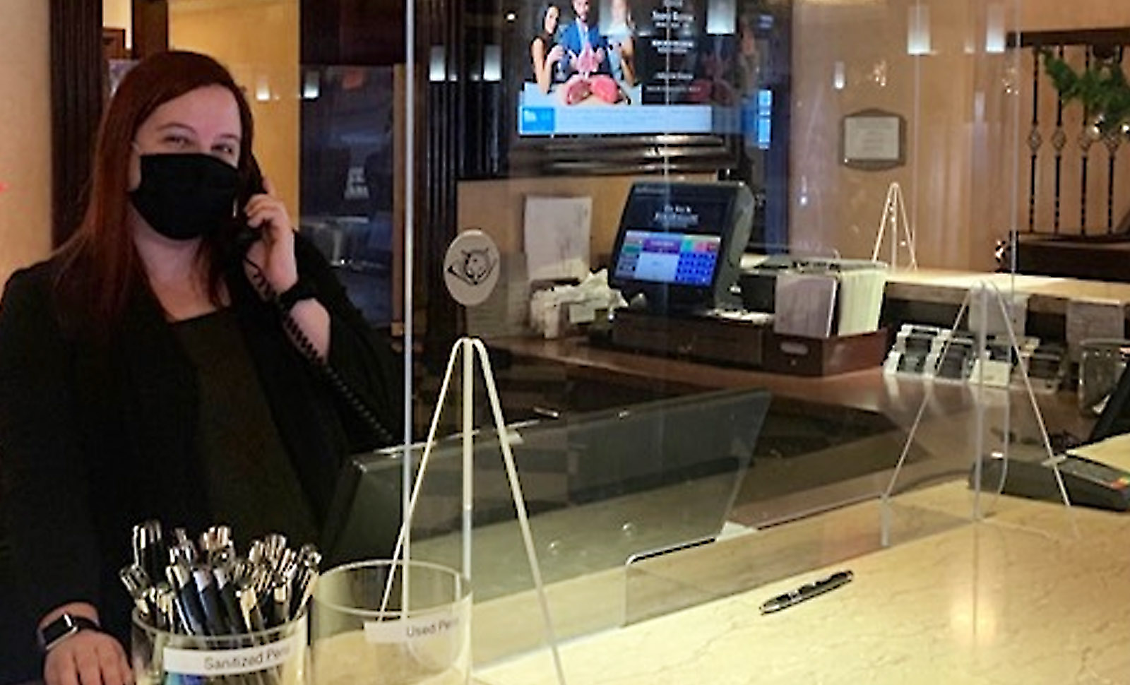 mask-wearing woman behind the hotel front desk smiling at the camera